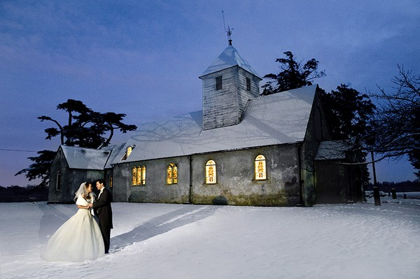 Bride and Groom Outside Chapel at Wasing Park in Berkshire in Snow