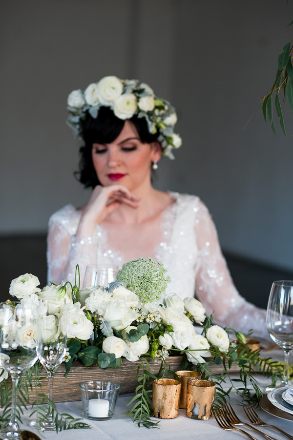 Bride with flower crown looking down at wedding table