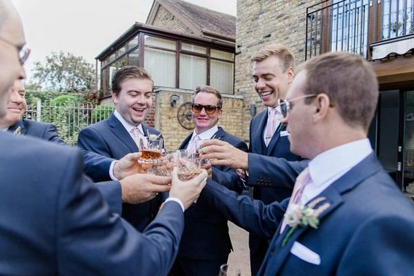 Groomsmen having a drink before wedding