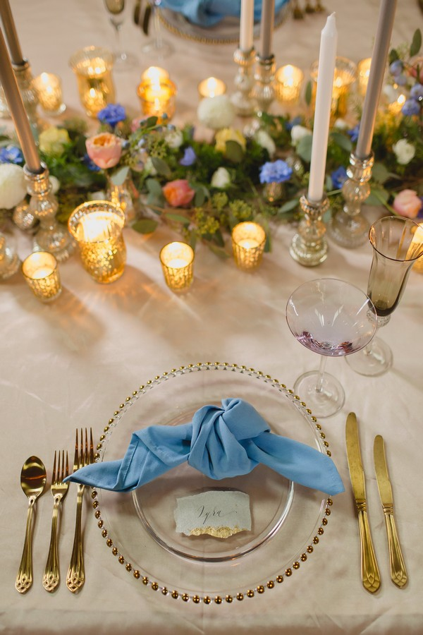 Wedding place setting with gold cutlery and blue napkin