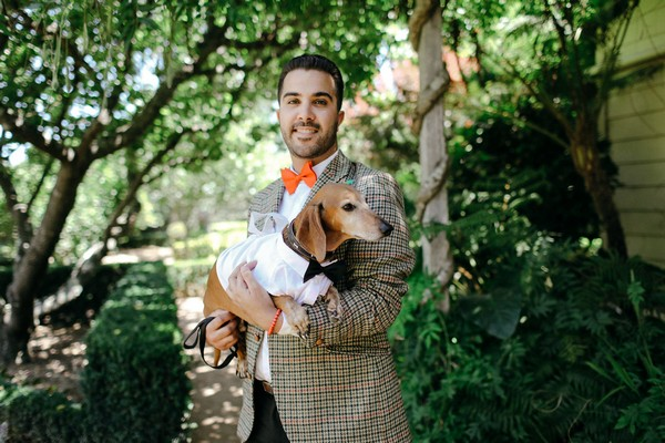 Man holding dog at wedding