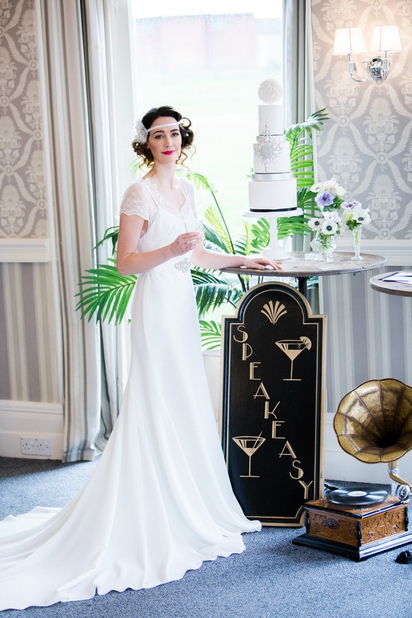 1920s bride holding drink standing next to wedding cake