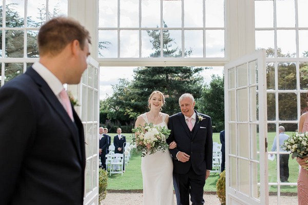 Groom turning to see bride approach altar