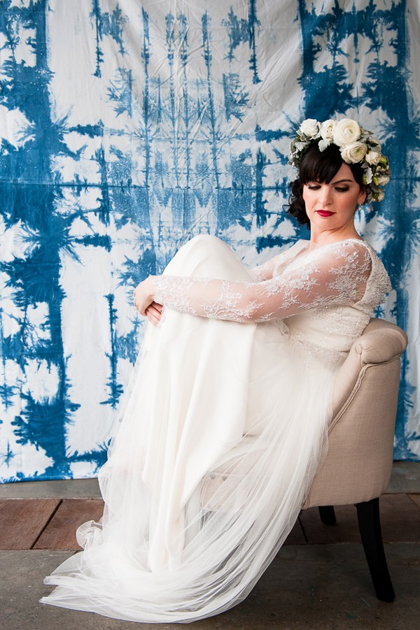 Bride sitting on chair with knees pulled up to her chest