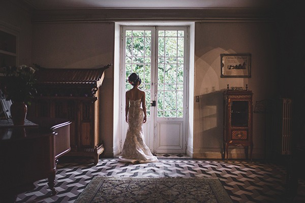 Bride standing looking out of window in door - Picture by Rik Pennington Photography