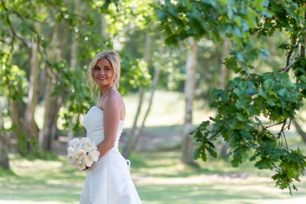 Bride under tree looking over her shoulder - Picture by Leanne Ashcroft Photography