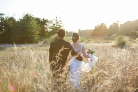 Back view of bride and groom walking though a field of wheat - Picture by Dos Clavos