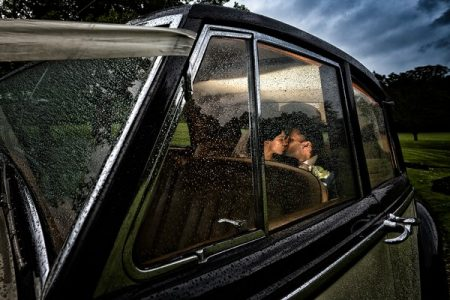 Bride and groom kissing in back of wedding car in the rain - Picture by Photography By Soven
