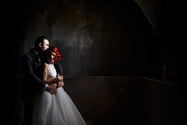 Groom hugging bride from behind in dark room - Picture by Marius Tudor Photography
