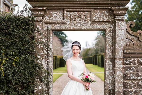 Bride standing in front of doorway in wall at Glamis Castle - Picture by Ally Stuart Photography