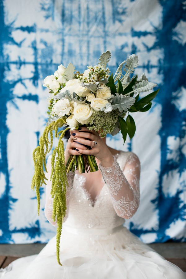 Bride holding wedding bouquet of white flowers and green foliage in front of her face