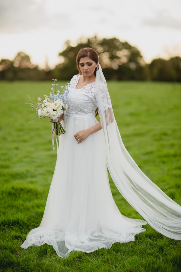 Bride wearing white wedding dress with long veil