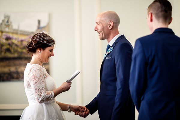 Groom holding bride's hand as she reads vows