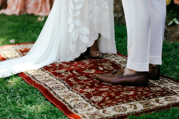 Bride and groom standing on rug during wedding ceremony