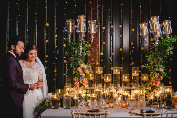 Bride and groom next to table covered in candles