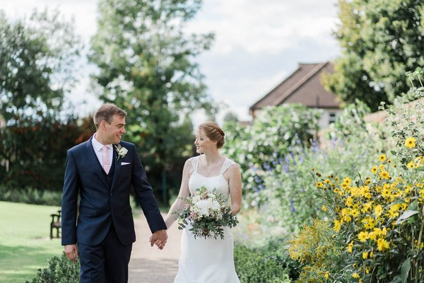 Bride and groom walking in gardens of Langtons House