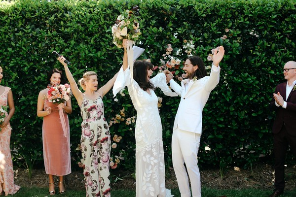 Bride and groom punching the air after getting married