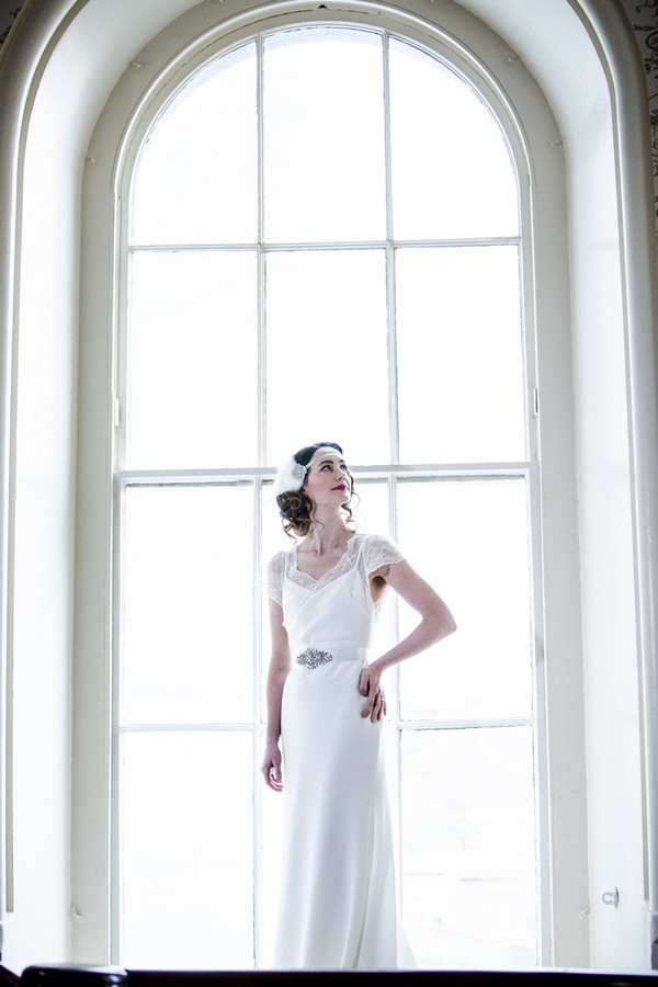 1920s bride standing in front of large window at The Duke of Cornwall Hotel