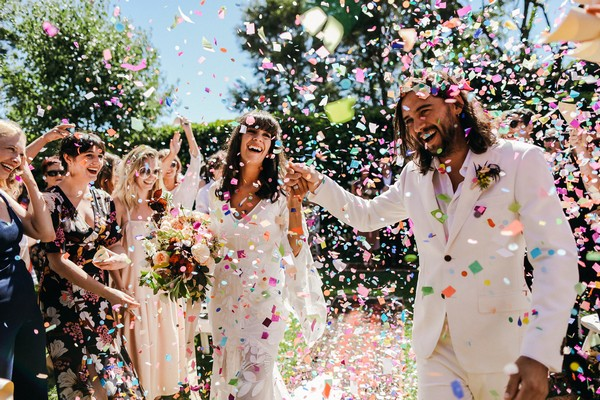 Bride and groom walking through shower of confetti