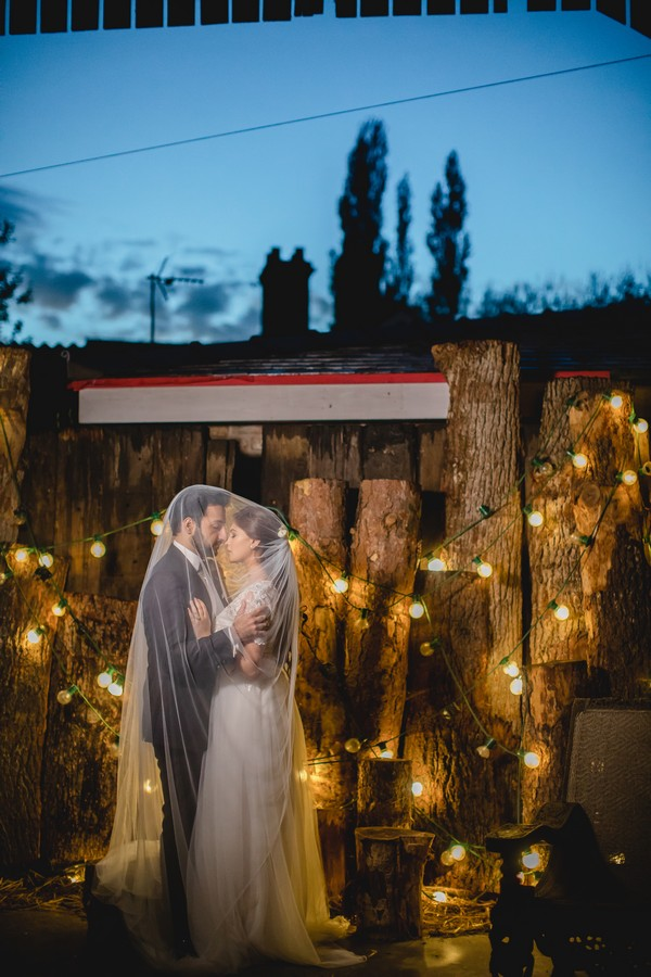 Bride and groom by logs covered in lights