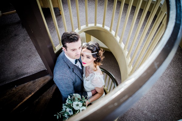 1920s bride and groom on spiral staircase at The Duke of Cornwall Hotel