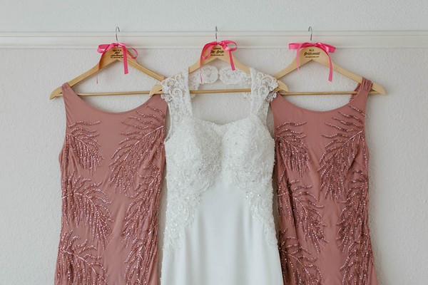 Wedding dress between muted pink bridesmaid dresses