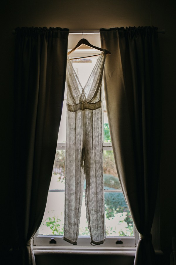 Bridal jumpsuit hanging in front of window