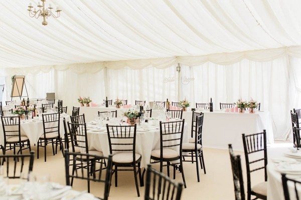 Wedding table with black chairs in marquee