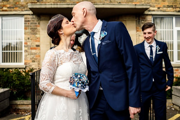 Bride and groom kissing outside registry office