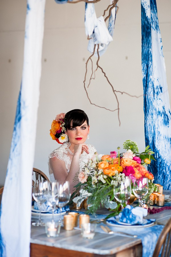 Bride sitting at wedding table with colourful flowers