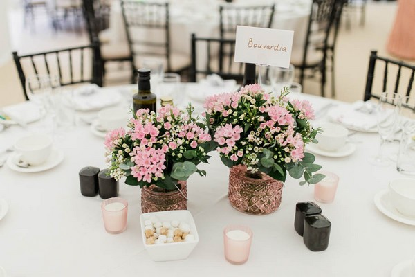 Pink flowers in copper pots on wedding table