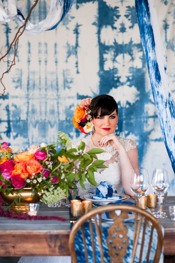 Bride sitting at wedding table with indigo Shibori backdrop