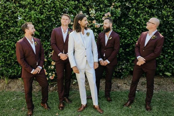 Groom with groomsmen in burgundy suits