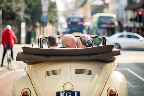 Bride and groom kissing in back of convertible VW Beetle wedding car