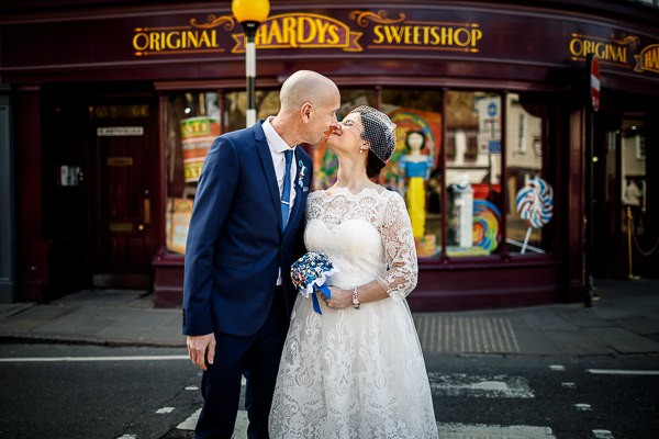 Bride and groom kissing outside sweet shop
