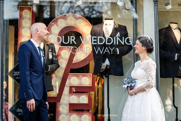 Bride and groom outside wedding shop
