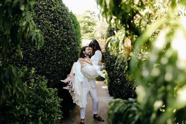 Groom carrying bride through gardens of Merribee