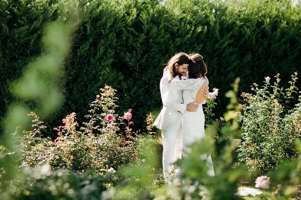 Bride and groom hugging in gardens of Merribee
