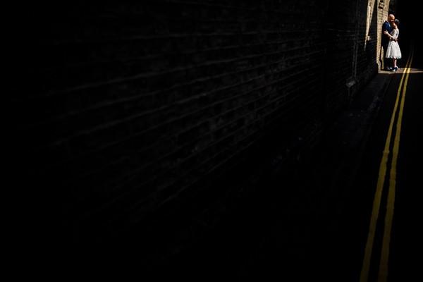 Bride and groom at end of dark alleyway