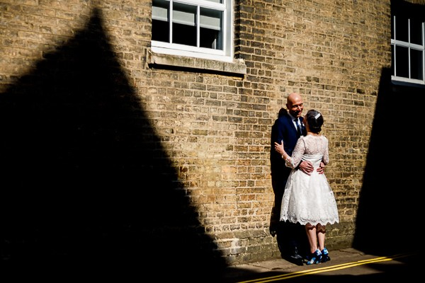 Bride and groom leaning against wall