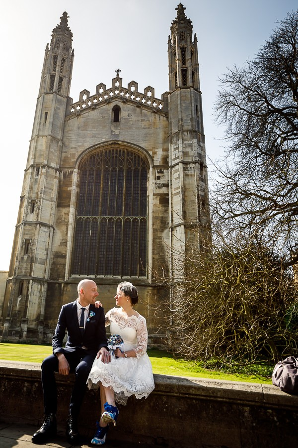 Bride and groom sitting on wall outside Cambridge Cathedral