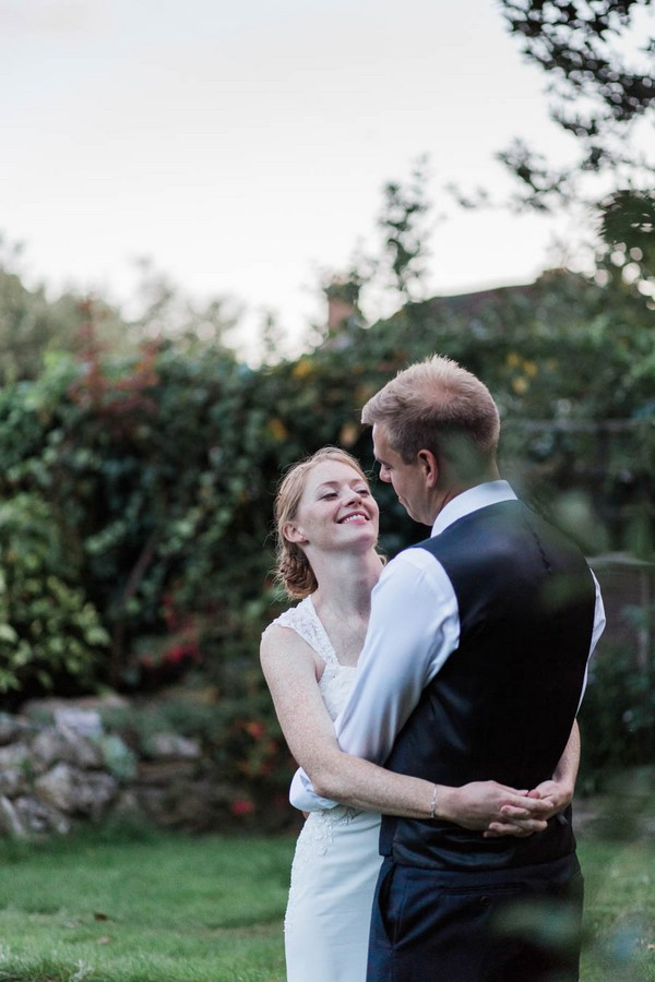 Bride and groom with arms around each other in their garden