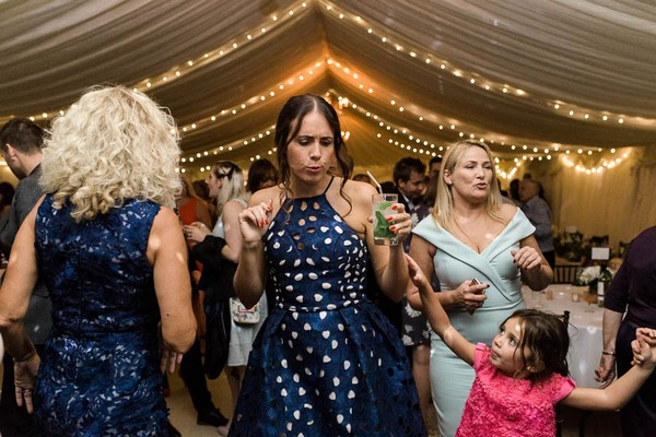 Wedding guests dancing in marquee