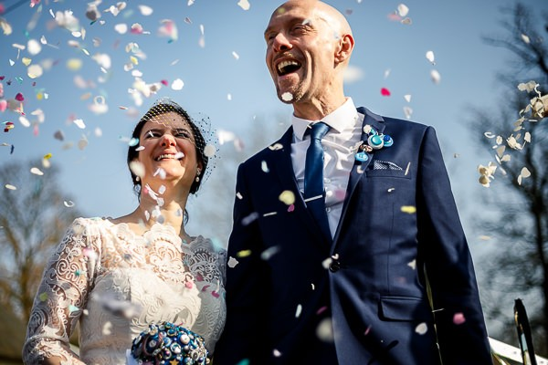Bride and groom being showered in confetti