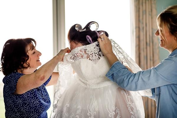 Women helping bride get dressed
