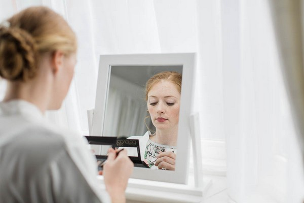 Bride doing make-up in mirror