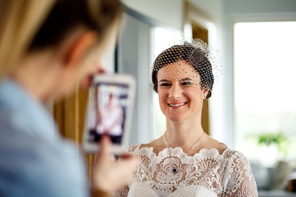 Bride smiling as friend takes picture on phone