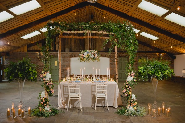 Wedding table with hanging florals and foliage above