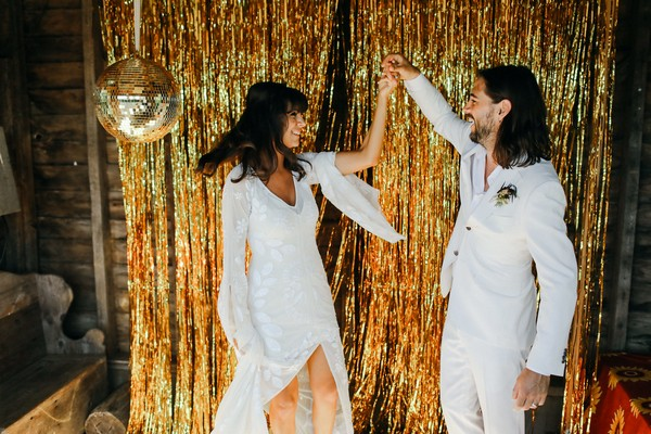 Bride and groom in front of gold sparkly backdrop with disco ball