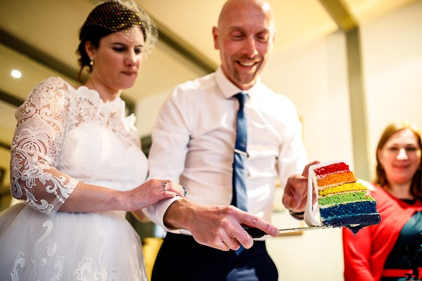 Bride and groom cutting rainbow wedding cake